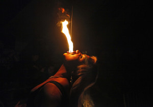 """In this July 7, 2013 photo, drag queen Susan Brown spits fire during her performance in the """"Fama"""" circus show in Santiago, Chile.  The only classic circus act in Fama is Brown's fire eating performance.  Fama has toured the country for more than a decade performing in modest tents and they say their show remains a refuge from discrimination. Chile has traditionally been a tough place for homosexuals. (AP Photo/Luis Hidalgo)"""